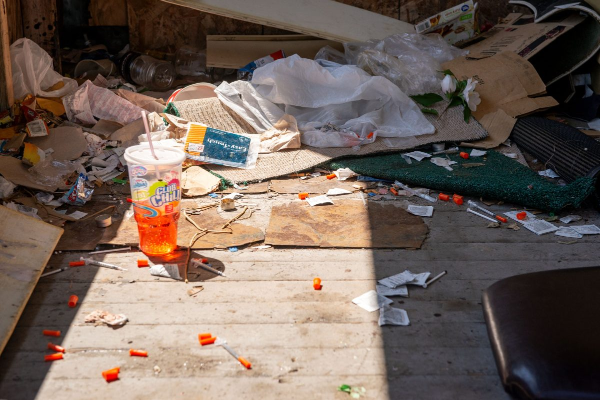 The porch of a vacant home on Berlin St. in Rochester is littered with used needles.