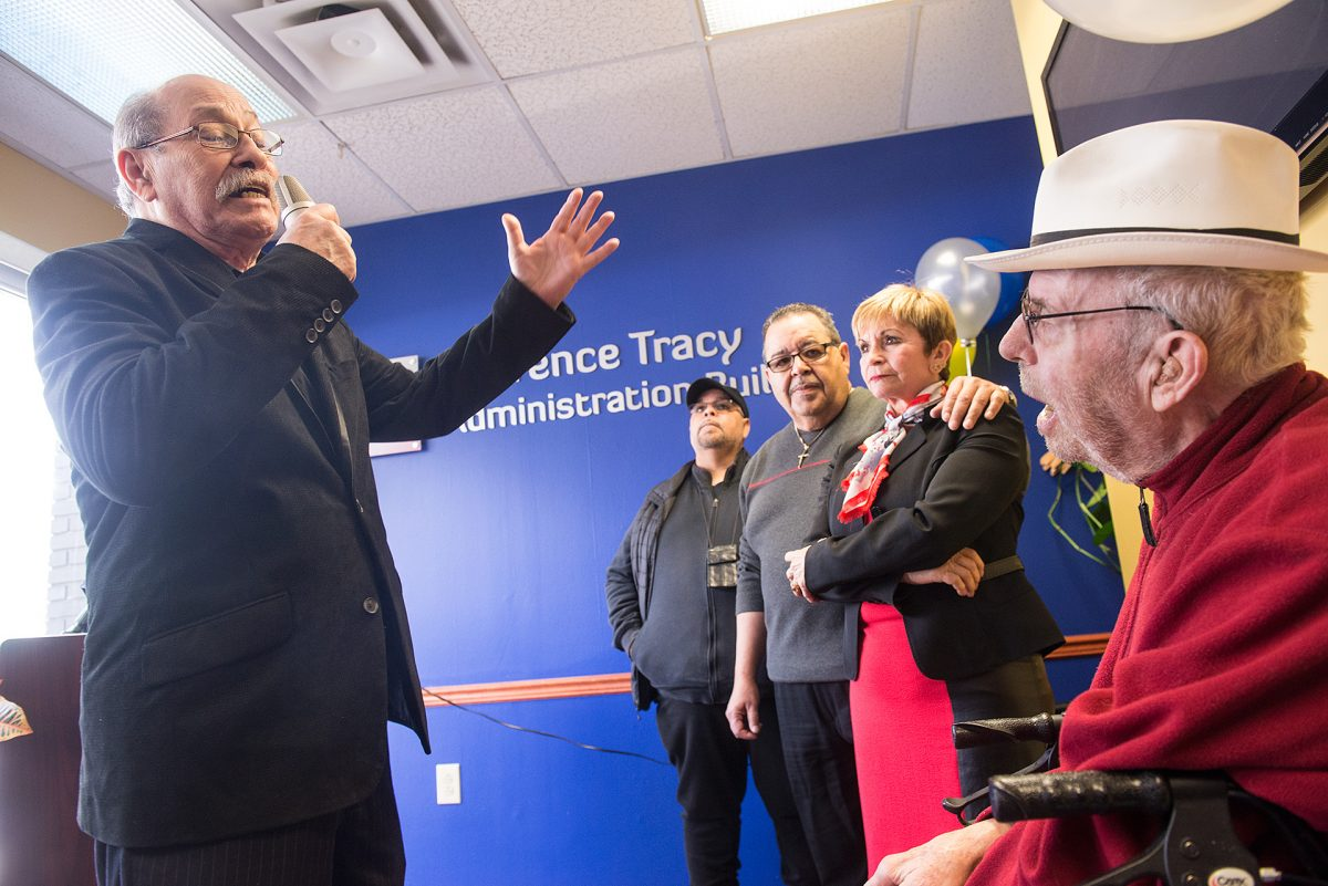 Johnny Vega sings an oringal song to Father Laurence Tracy during a ceremory to rename IBERO offices in honor of Tracy on Feb. 13 in Rochester. Tracy is a founding member of Ibero-American Action League EMC Photo by John Haeger