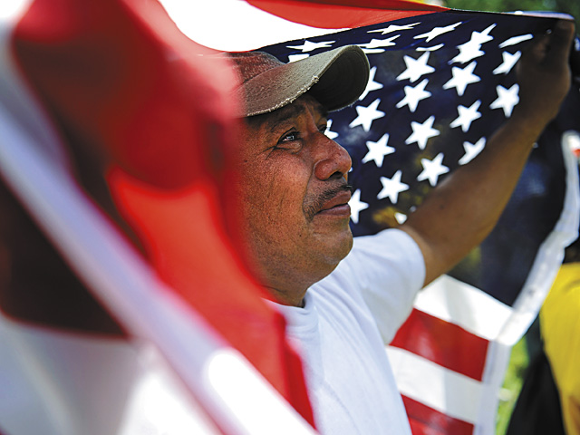 Amilcar Ramirez weeps as he holds a U.S. flag at a May Day rally in Washington May 1. Demonstrators at rallies across the nation criticized Arizona's new immigration law which makes it a state crime to be in the United States illegally. (CNS photo/Jonathan Ernst, Reuters) (May 3, 2010) See IMMIGRATION-RALLIES May 3, 2010.
