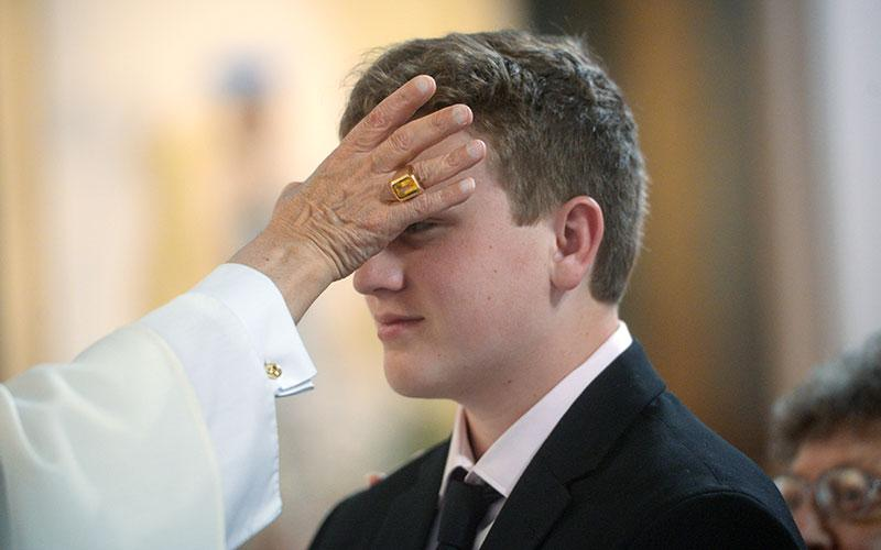 Bishop Salvatore R Matano anoints the forehead during the celebration of the Sacrament of Confirmation on May 16, 2019 in Ithaca. (Courier file photo)