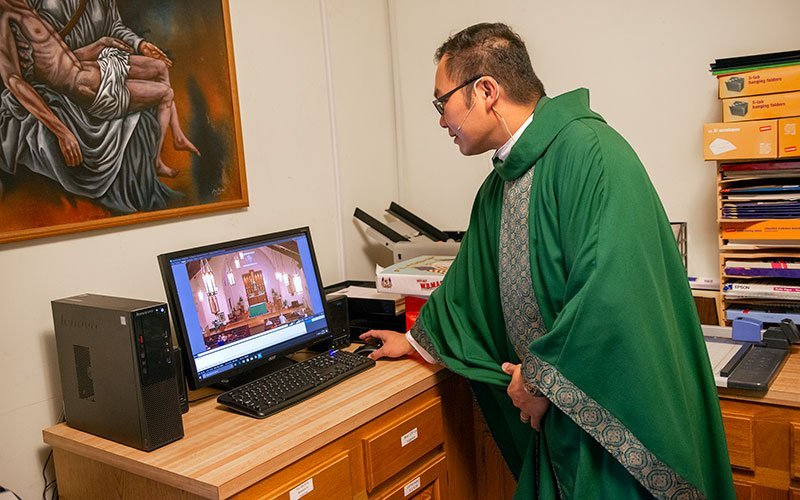 Father Edison Tayag begins the YouTube livestreaming of an Oct. 21, 2017, Mass at St. Patrick Church in Victor. (File photo)