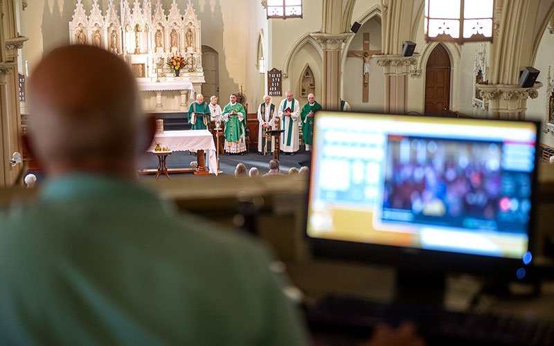 Video operator Mike Paulin looks over the camera feed during a Sept. 15, 2018, Mass at St. Mary Church in Corning. (EMC file photo)