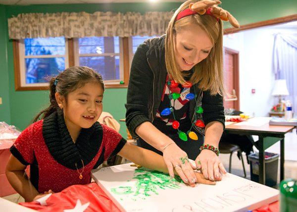 Heidi Franco-Lopez (left) and Emily Hanehan contribute to a handprint Christmas tree.