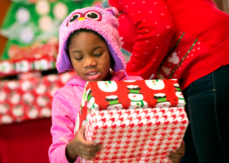 Taneisha Jackson carries away the gifts given to her by Santa Claus during the fiesta.
