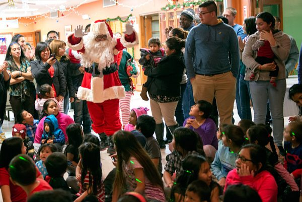 Santa Claus enters the dance floor to hand out gifts to the children in attendance.