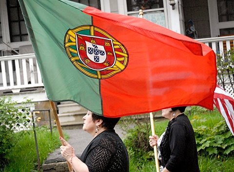 Belmira Gouveia carries the Portuguese flag during the procession.