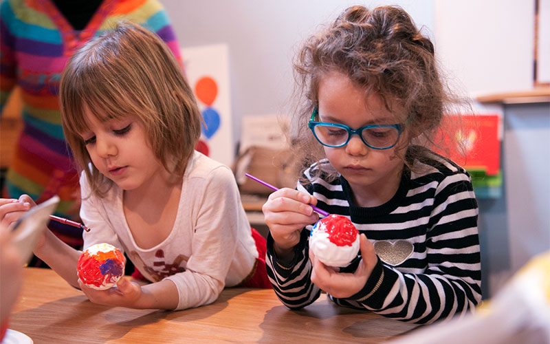 Four-year-old Everleigh Lake (left) and 5-year-old Brynlee Herford paint pinata parts at Hipocampo Books in Rochester Dec. 14. (Photo by Greg Francis)