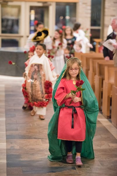 Seven-year-old Emilia Nicolay-Carrera leads a rose procession prior to the presentation of the gifts during a Dec. 12 Mass celebrating Our Lady of Guadalupe at St. Joseph Church in Penfield.