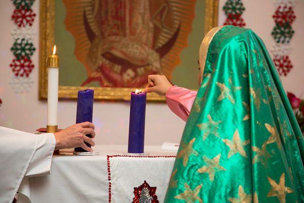 Sharon Jaramillo lights a candle during Mass.