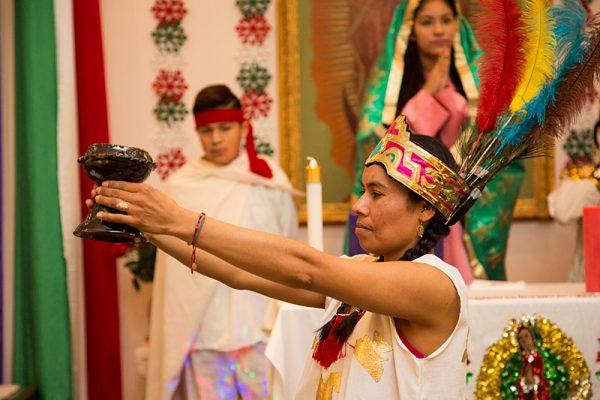 Playing an indigenous woman, Beatriz Trejo prepares an offering for Our Lady of Guadalupe during the celebration.