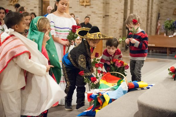 Children place roses near the altar prior to the presentation of the gifts during a Dec. 12 Mass celebrating Our Lady of Guadalupe at St. Joseph Church in Penfield.