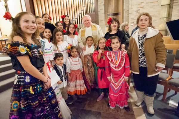 Children participating in the Our Lady of Guadalupe celebration at St. Joseph Church in Penfield Dec. 12 pose with Father James Schwartz at the end of Mass.