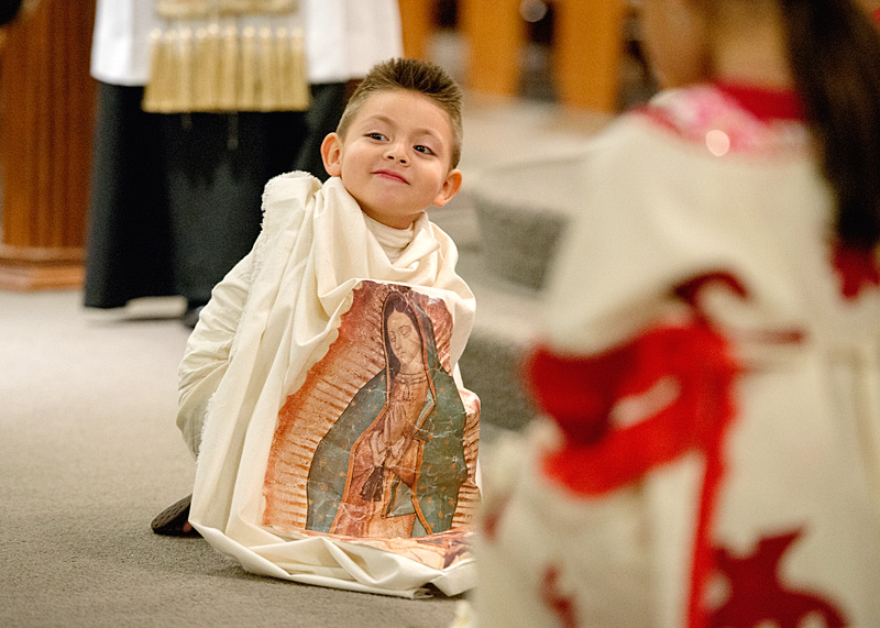Portraying St. Juan Diego, 4-year-old Alan Carbajal watches as people approach the altar to place roses by an image of Our Lady of Guadalupe.