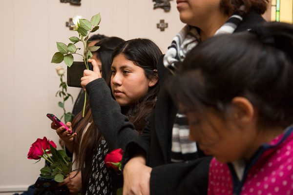 Isis Hernandez takes a video of the Mass.