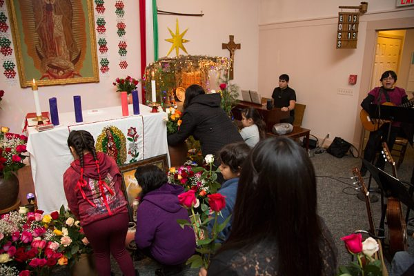 Members of Guadalupe Mission Church bring roses to the altar during the celebration.