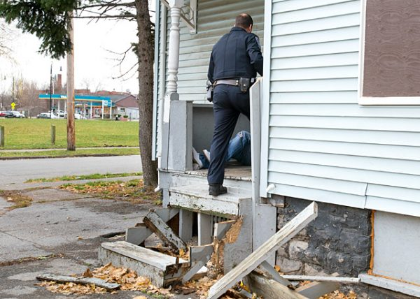 Rochester City Police Capt. Kevin Costello confronts a heroin user outside an unoccupied residence on Sullivan Street during a foot patrol of the North Clinton neighborhood Dec. 1.