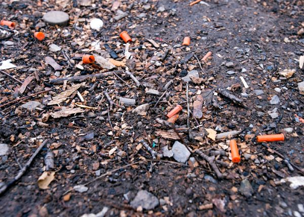 Orange caps used to cover needles litter the ground near in a lot near North Clinton Avenue.