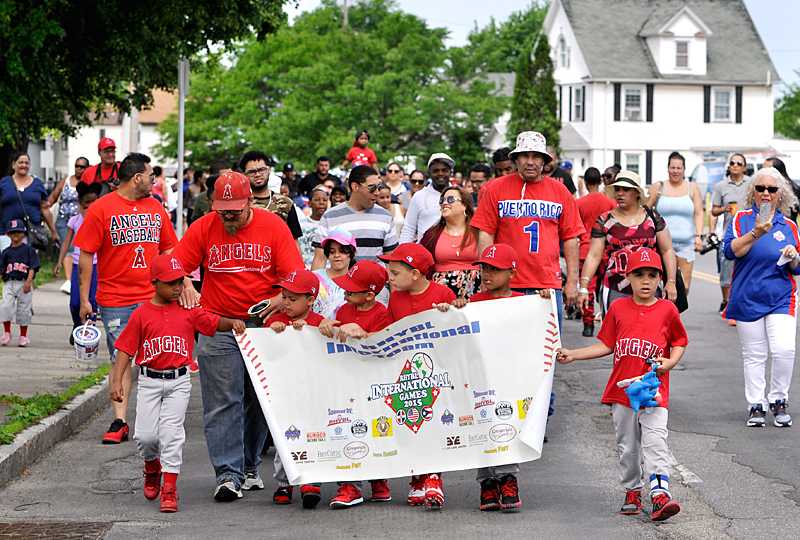Players, coaches and family members makes their way toward Baden Street Park during a parade that was part of the opening day festivities for the Rochester Hispanic Youth Baseball League June 4.