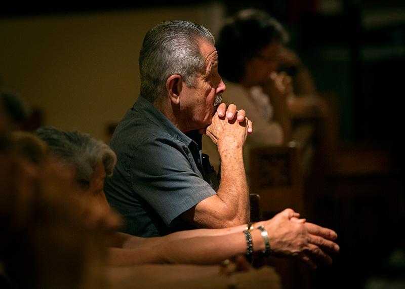 Rufino Pabon kneels in prayer during Mass.
