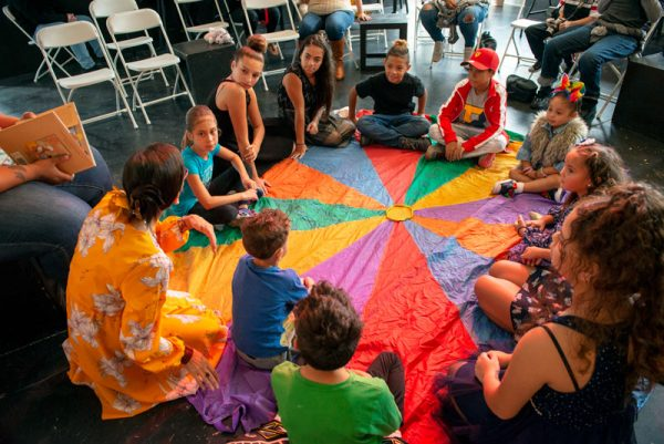 Children sit in a circle during a book reading at the Oct. 6 event at The Avenue Blackbox Theatre.