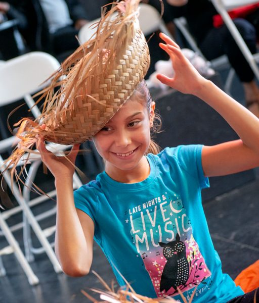 Eight-year-old Juliana Vásquez-Colindres tries on a straw hat during the Oct. 6 event at The Avenue Blackbox Theatre.