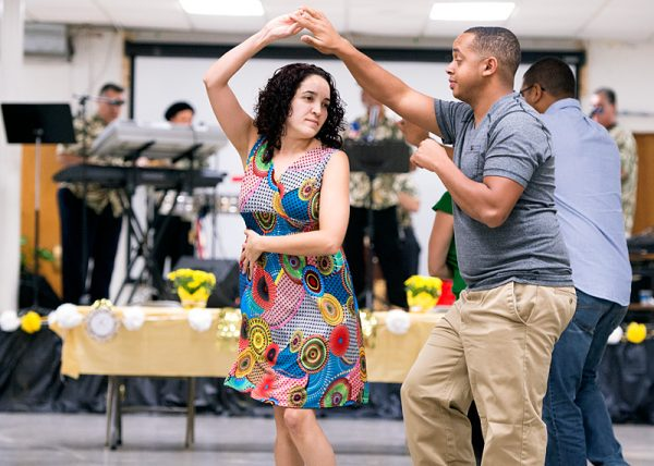Nelissa Pérez (left) and Francisco Restitullo dance during the celebration following Mass.