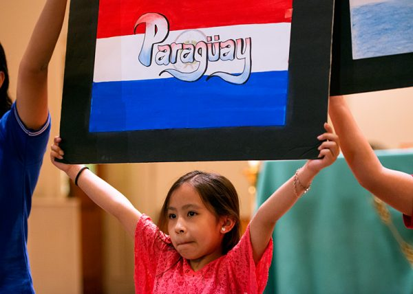 Nine-year-old Isabella Collon holds up the Paraguayan flag after processing into Mass.