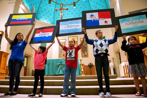 Children hold up flags of Latin American countries in celebration of Hispanic Heritage Month.