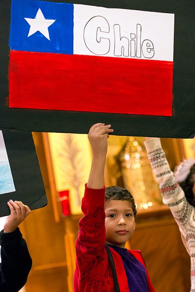Charlie Figueroa-Ortiz holds up the Chilean flag after processing into Mass.