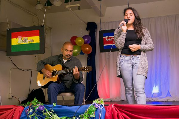 Orlando Nuñez (left) plays guitar while Selmary Madera sings in the church hall.