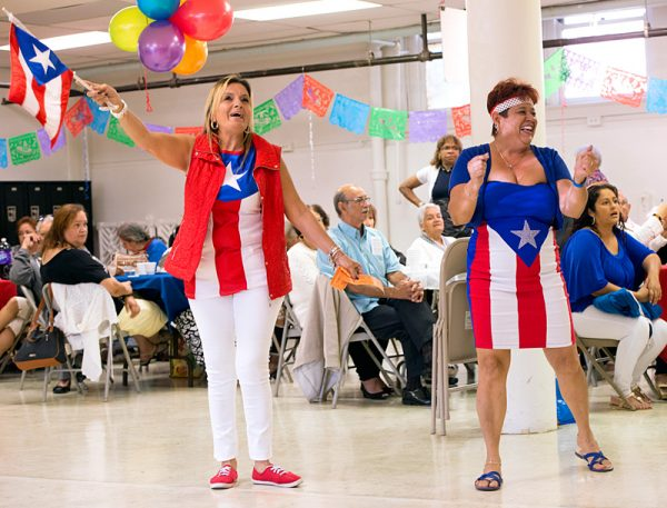 Dolly Ruiz (left) and Maria Pagan dance to music in the church hall following Mass.