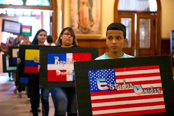 Javier Torres processes into Mass carrying the American flag.