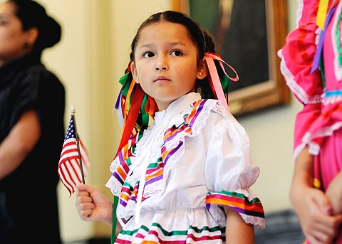 Nyssa Vilchis, 6, holds a flag during the National Anthem.