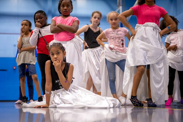 A girl takes a break while learning a dance.