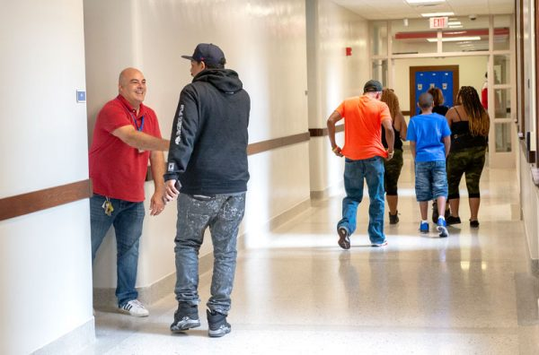 Teacher stands outside of his classroom to greet visitors.