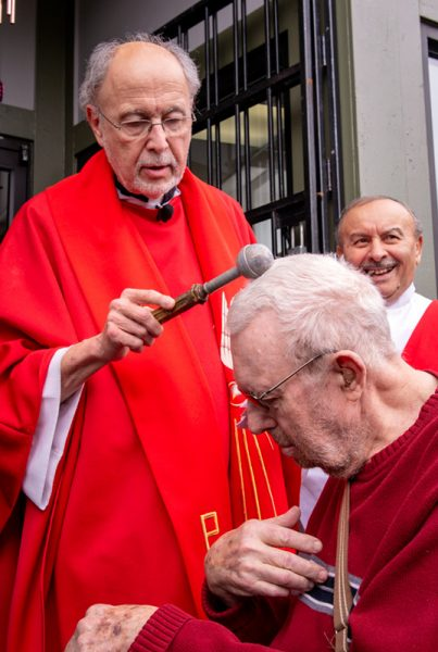 Father Werth blesses Father Tracy.