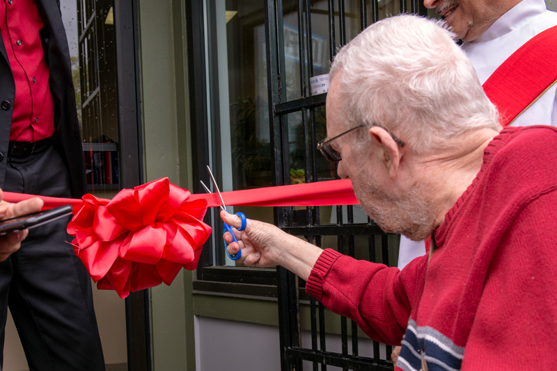 Father Tracy cuts the ribbon.