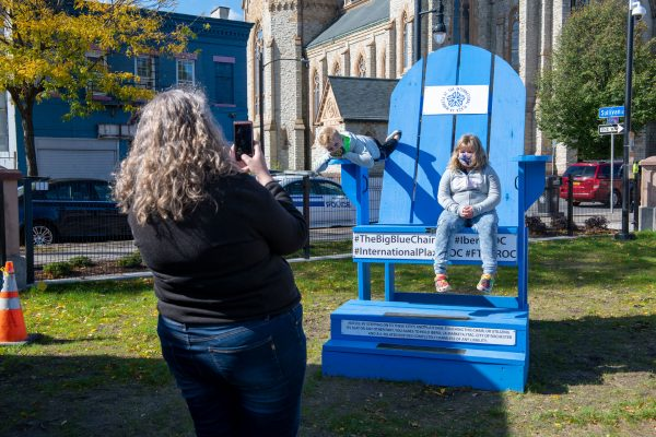 Bridget Nowak takes a photo of her children Jamie and Claire on the big blue chair at the market.