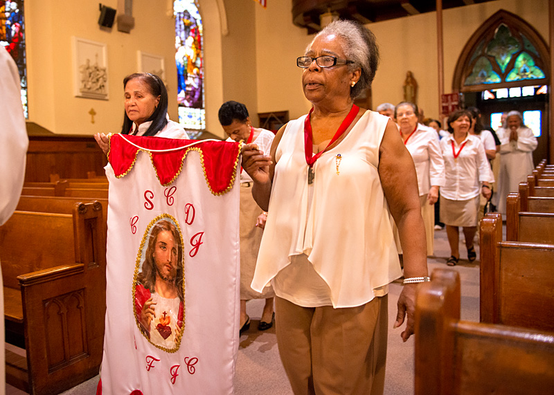 Antonia Hernandez (left) and Fanny DeJesus of the group of the Sacred Heart process into Rochester's Holy Apostles Church for a June 23 Mass celebrating the feast day of St. John the Baptist.
