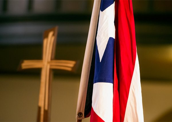 A Puerto Rican flag and cross is carried during the procession at the June 24 Mass at Rochester's Our Lady of the Americas Church.