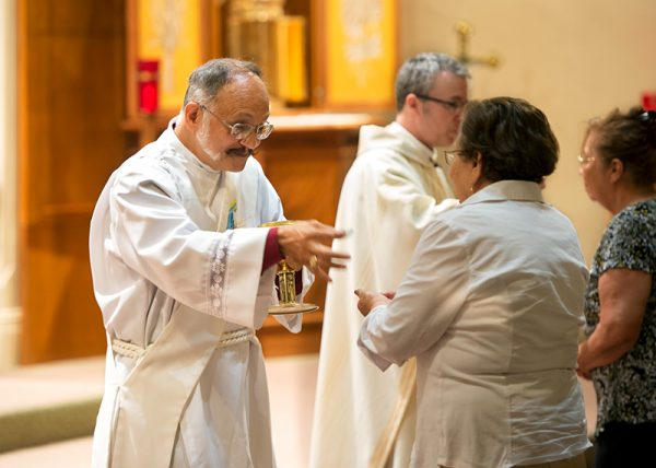 Deacon Carlos Vargas distributes the Eucharist during the Mass in honor of Saint John the Baptist.