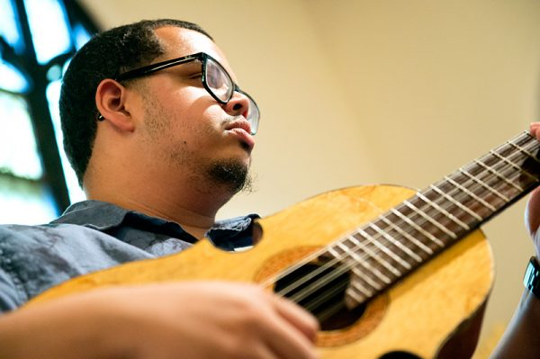Xavier Torres plays guitar with the choir during Mass.