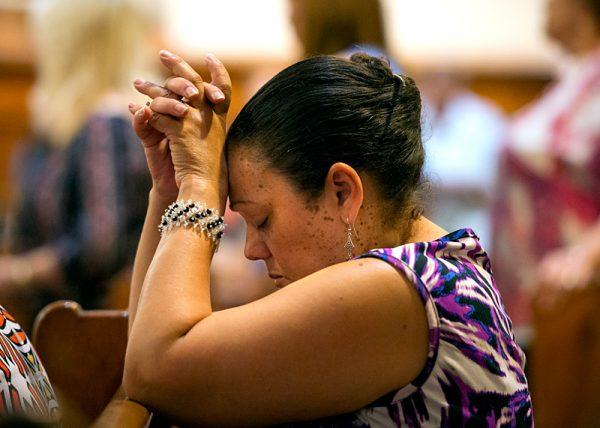 Wanda Medina kneels in prayer during the Liturgy of the Eucharist.