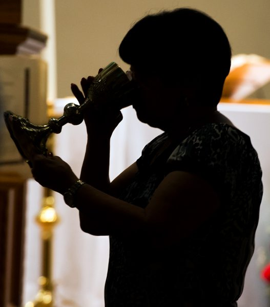 A Mass attendee takes communion during Mass.