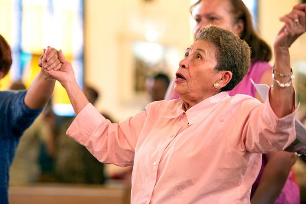 Gloria Perez joins hands with congregants in prayer.