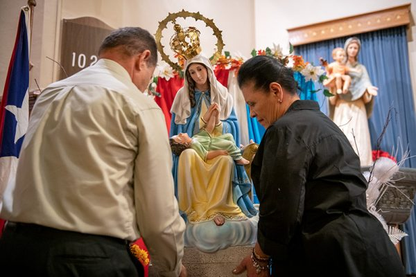 Manuel and Maria Rodriguez set down a statue of Our Lady of Providencia at Rochester's Holy Apostles Church Nov. 19 during a Mass celebrating the patroness of Puerto Rico.