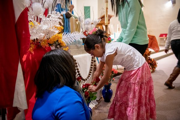 Seven-year-old Danna Camila places a flower in front of the statue.
