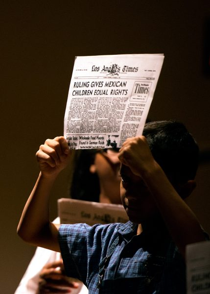 """A boy holds up a newspaper during the performance of """"Separate Is Never Equal,"""" a play based on the story of civil rights activist Sylvia Méndez."""