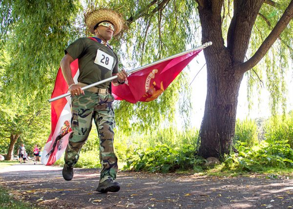 William Rodriguez carries Marine and Puerto Rican flags during the race.