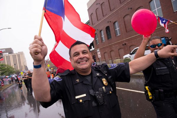 Members of the Rochester City Police Department wave to the crowd as they march in the annual Puerto Rican Parade Aug. 17.